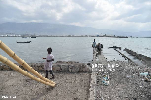 Children play near a wharf in the commune of Cite Soleil PortauPrince on March 14 2018 Book by book and with donations large and small some from...