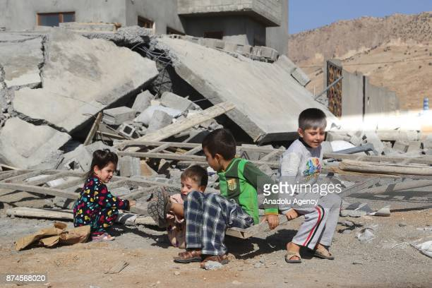 Children play near debris of a building at Darbandikhan district of Suleymaniyah after an earthquake measuring 73 on the Richter scale rocked...