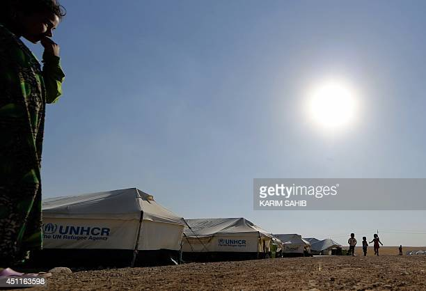 Children play near tents in a camp for displaced Iraqi Shiite Turkmen who fled their town of Tal Afar in Shikhan in Kurdistan's Dohuk province on...