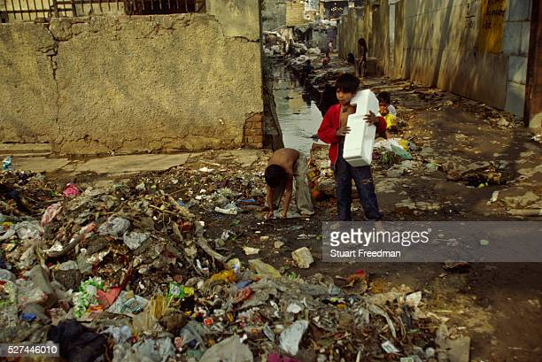 'Children play near the open sewer in the Shadipur Depot slum One boy uses a piece of polystyrene as a drum Shadipur Depot an industrial area in West...