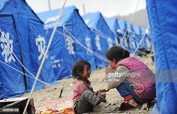 Children play near their temporary tents at the earthquake-hit Gyegu town of Yushu County, Qinghai province April 18, 2010. VCP