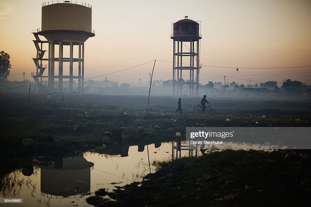 Children play near water towers in front of their homes near the Union Carbide factory on November 27, 2009 in Bhopal, India. Twenty-five years after an explosion causing a mass gas leak, in the Union Carbide factory in Bhopal, killed at least eight thousand people, toxic material from the biggest industrial disaster in history continues to affect Bhopalis. A new generation is growing up sick, disabled and struggling for justice. The effects of the disaster on the health of generations to come, both through genetics, transferred from gas victims to their children and through the ongoing severe contamination, caused by the Union Carbide factory, has only started to develop visible forms recently.