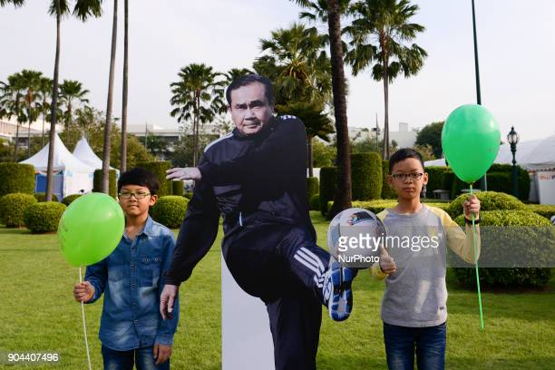 Children play next to a cardboard cutout of Thailand's Prime Minister Prayuth Chanocha during the Children's Day celebration at Government House in...