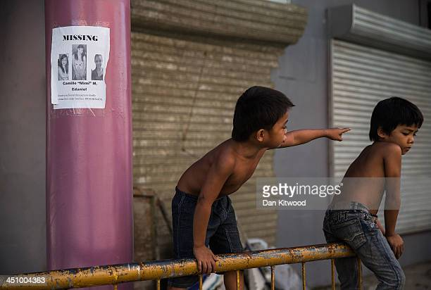 Children play next to a 'missing persons' poster on November 21 2013 in Leyte Philippines Typhoon Haiyan which ripped through Philippines over a week...