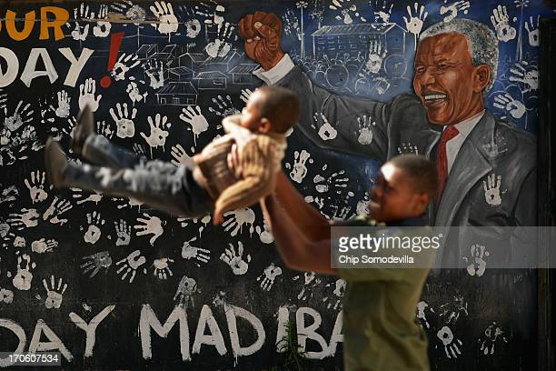 Children play next to a mural depicting former South African President Nelson Mandela near where he lived during the 1940s in Alexandra Township June...