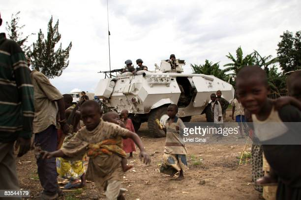Children play next to a United Nations convoy heading to Rutchuro to relaunch UN operations in the area north of the provincial capital of Goma on...