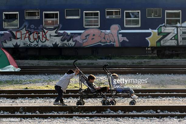 Children play next to railway tracks at the refugee and migrant makeshift camp on the GreekMacedonia border near the village of Idomeni on May 23...