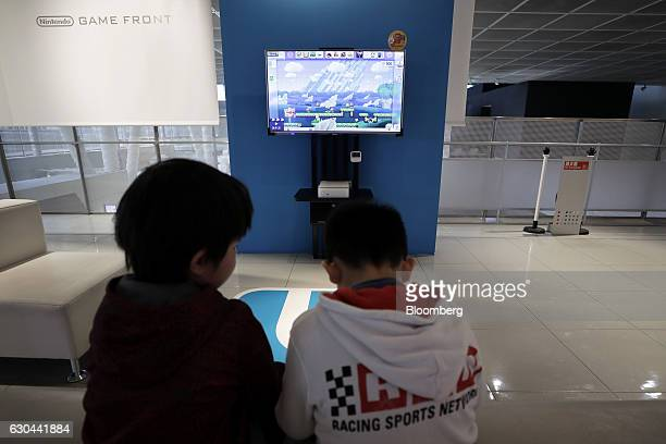 Children play Nintendo Co's Super Mario Maker video game using the company's Wii U game console controllers at the Nintendo Game Front showroom in...