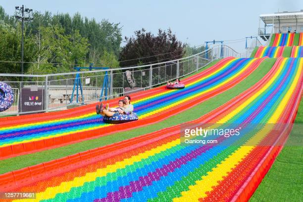 Children play on a 103-meter-long rainbow slide at Wukesong's Bloomage LIVE Square on July 22, 2020 in Beijing, China.