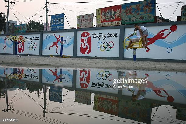 Children play on a bodybuilding equipment in front of a billboard paintings that are displayed on the walls to promote the 2008 Olympics on August...