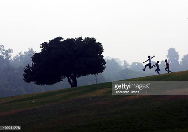 Children play on a foggy and cold morning at Raj Ghat on November 28 2015 in New Delhi India Dense fog continued to disrupt normal life in North...