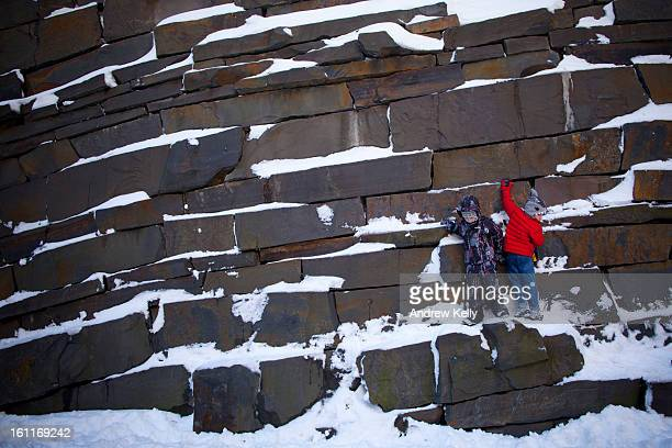 Children play on a rock wall covered in snow following a major winter storm on February 9 2013 in New York City New York City and much of the...