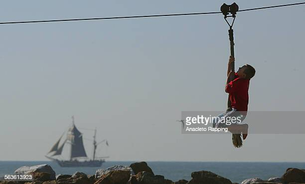 Children play on a rope swing attached to a pulley in Marina Park on 2/18/03 One of two Historic tall ships visiting Ventura harbor passes by in...