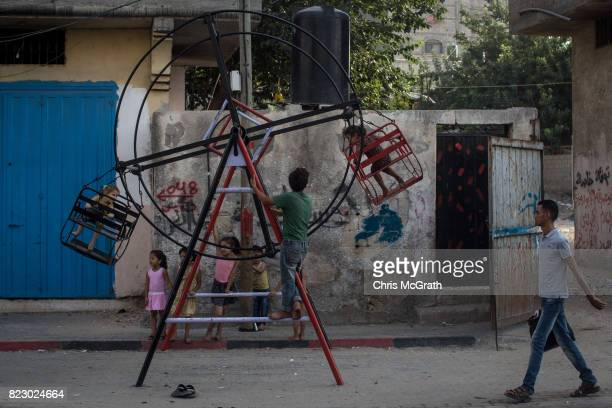 Children play on a small manual ferris wheel on July 23 2017 in Gaza City Gaza For the past ten years Gaza residents have lived with constant power...
