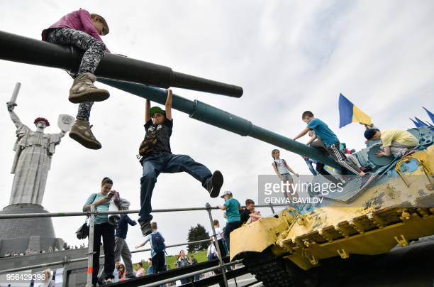 Children play on a Sovietera tank during a ceremony marking Victory Day at the WWII openair in museum in Kiev on May 9 2018