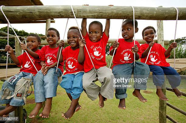 Children play on a swing at a community creche for disadvantaged children whose parents are HIVpositive March 1 2004 in East London South Africa A...