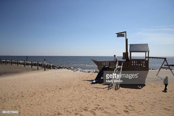 Children play on a wooden ship on the shore of the Chesapeake Bay on March 17 2017 in North Beach Maryland Under US President Donald Trump's 2018...