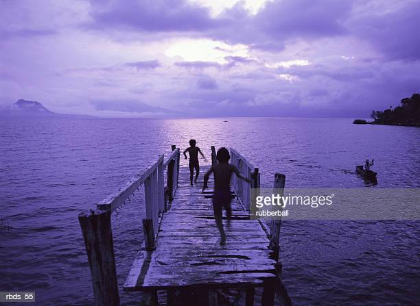 children play on an old weathered dock as a man rows to shore