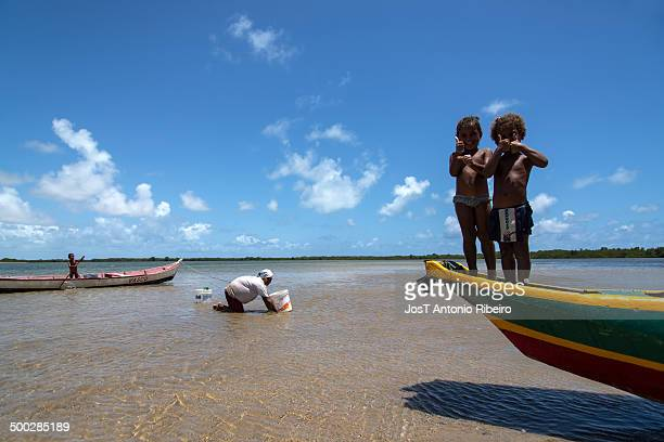 Children play on boats in the rivers of Mangue Seco while mom collects clams for lunch.