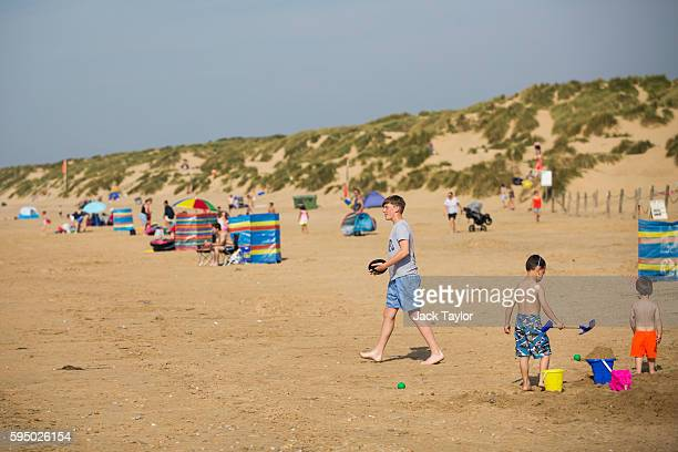 Children play on Camber Sands on August 25 2016 in Rye England Five men were found dead after being pulled from the sea on the hottest day of the...