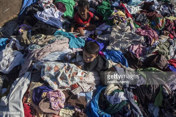 Children play on pile of clothes which are donated for people affected by earthquake at a temporary shelter in Lombok Indonesia on August 13 2018...