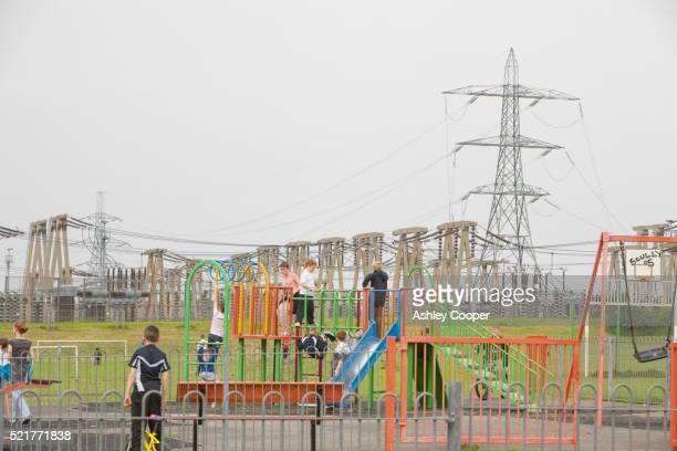 Children Play on Playground Near Power Plant