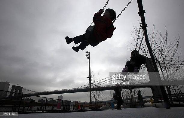 Children play on swings after a ribbon-cutting ceremony for the just-opened first section of Brooklyn Bridge Park March 22, 2010 in the Brooklyn...