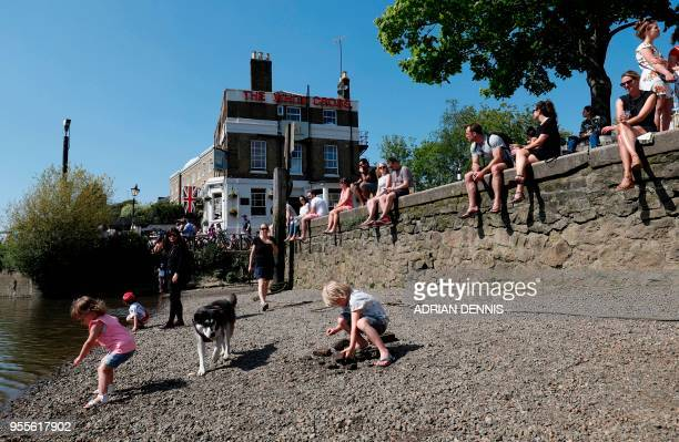 Children play on the banks of the River Thames as they soak up the sun in Richmond south west London on May 7 2018 Temperatures on Monday were...
