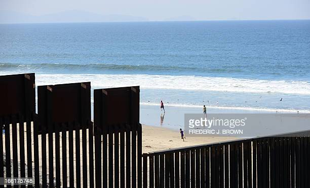 Children play on the beach at Playas de Tijuana Mexico across the 'border fence' which runs along the USMexico border some three hundred feet into...