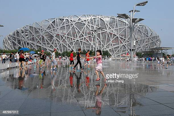 Children play on the fountain in front of the China National Stadium on August 5 2015 in Beijing China 15th IAAF World Championships will be held on...