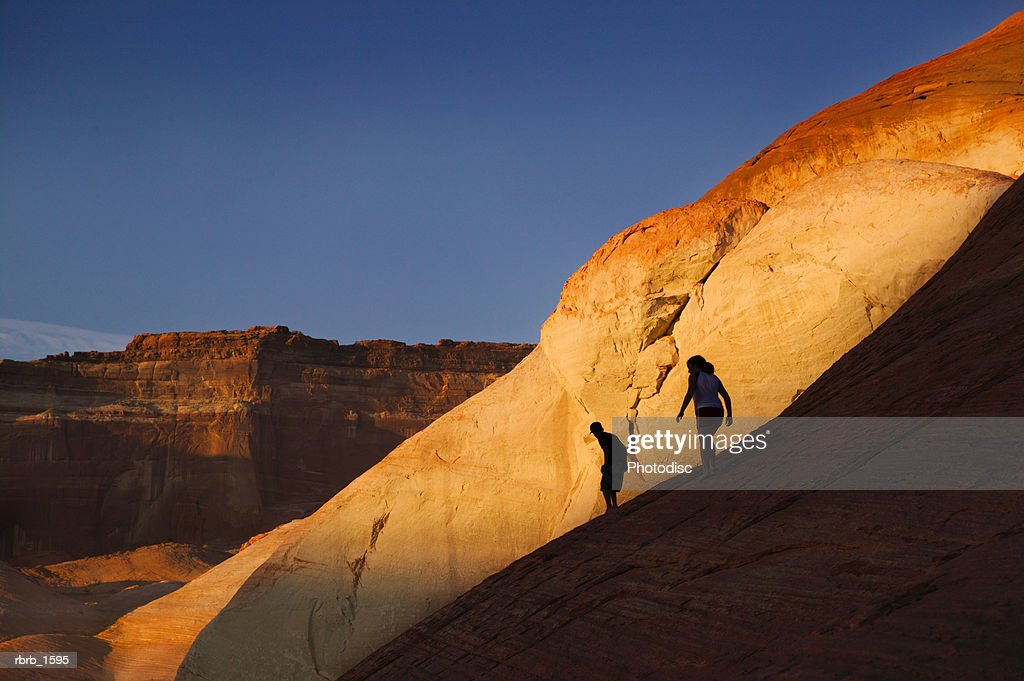 children play on the red rocks during sunset in a rural southwest setting : Stockfoto