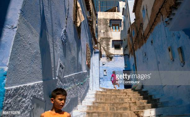 Children play on the steps in the Medina of the northwestern Moroccan city of Chefchouen in the northern Rif region on September 19 2017 Huddling...