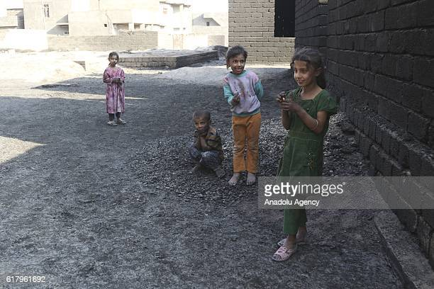 Children play on the streets after an oil well set on fire in the center of al-Kayyara town to the south of Daesh terror organization-held Mosul in...