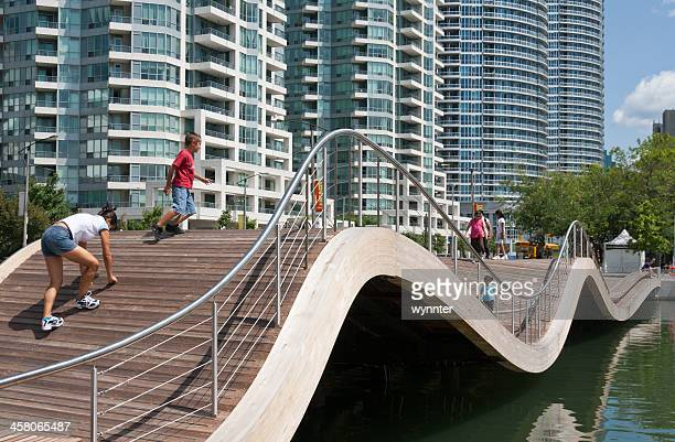 children play on wavedeck at toronto's harbourfront centre in summer - waterfront stock pictures, royalty-free photos & images