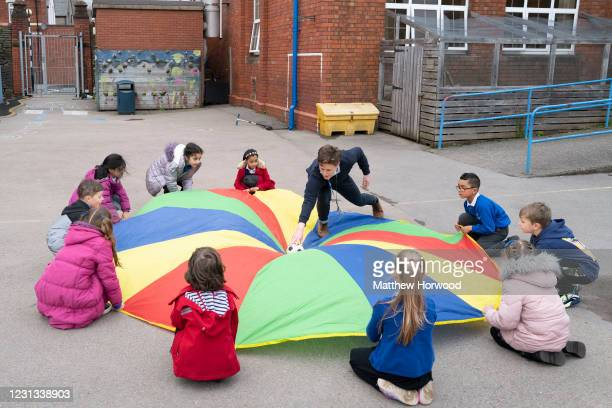 Children play outdoors with a multicoloured parachute at Roath Park Primary School on February 23, 2021 in Cardiff, Wales. Children aged three to...