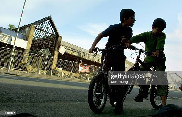 Children play outside an automobile showroom which has burned down in the Manningham District of Bradford July 14 2001 in London England The...