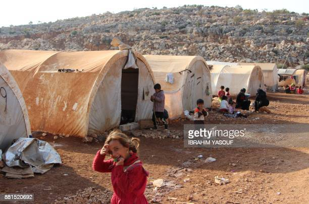 Children play outside tents at the Furat camp for the displaced from Deir Ezzor north of the town of Kafr Dariyan in the countryside of the northern...
