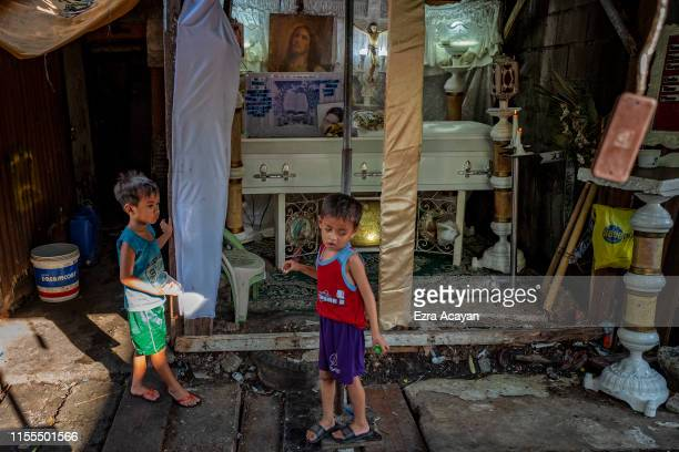 Children play outside the funeral wake of John Ryan Marquez on July 13 2019 in Malabon Metro Manila Philippines According to police Marquez was...