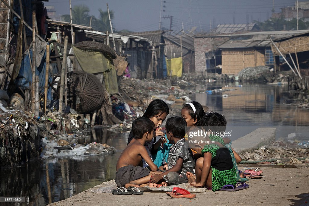 Children play outside their home, next to a polluted canal which empties out into the Buriganga river, November 10, 2013 in the Hazaribagh neighborhood of Dhaka, Bangladesh. Hazaribagh was just listed in a report by Green Cross Switzerland and Blacksmith Institute as the 5th most polluted place on earth. It houses 95% of Bangladesh's leather tanneries, and every day they dump 22,000 cubic liters of toxic waste, including the cancer-causing hexavalent chromium, into the capital city's main river and key water supply, the Burgiganga. Most of the laborers work with the hazardous chemicals without any safety precautions, and there have been reports of horrific workplace accidents in the factories. Residents of the neighborhood slums are exposed to the extreme air, water and soil pollution. The tanneries export millions of dollars of leather good around the world, including the US and Europe.