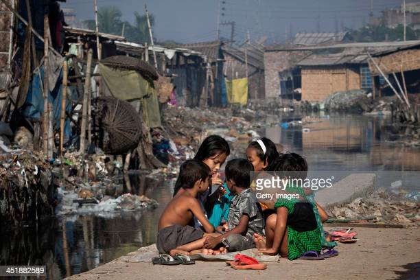 Children play outside their home next to a polluted canal which empties out into the Buriganga river November 10 2013 in the Hazaribagh neighborhood...