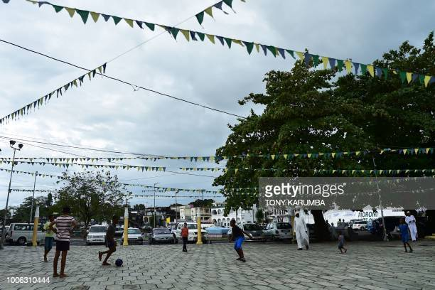 Children play soccer at a square lined with pennants close to the port at Moroni on July 27 2018 where an upcoming referendum has caused political...