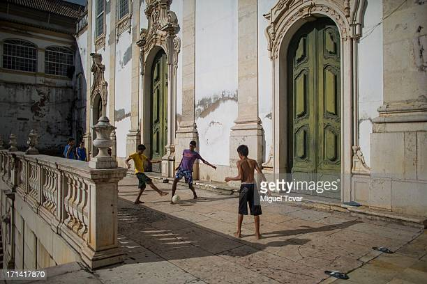 Children play soccer outside a church of Salvador host city of FIFA Confederations Cup Brazil 2013 on June 23 2013 in Salvador Brazil