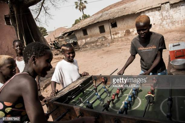 Children play table football in the Mindara neighbourhood in Bissau on Mardi Gras on February 13 2018 / AFP PHOTO / Xaume Olleros