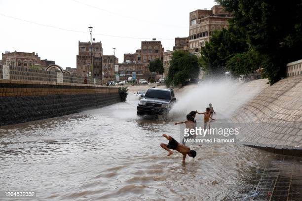 Children play through a flooded street after heavy rainfalls on August 06, 2020.