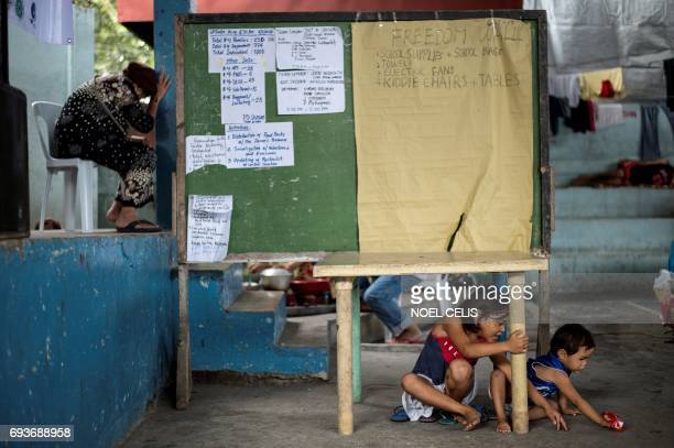Children play under a table inside a covered basketball court turned into an evacuation center for the Marawi City evacuees at Maria Cristina...