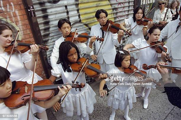 Children play violins outside Old St Patrick's Cathedral during memorial service for John F Kennedy Jr his wife Carolyn Bessette Kennedy and her...