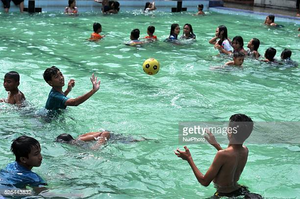 Children play water and take a bath at the public bath during Javanese tradition called Padusan in Solo Central Java Indonesia on June 27 Held once a...