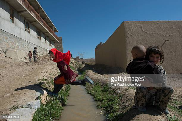 Children play while Afghan Army General Abdul Razeq surveys a village where recent kidnappings and Taliban activities have occurred in the Village of...
