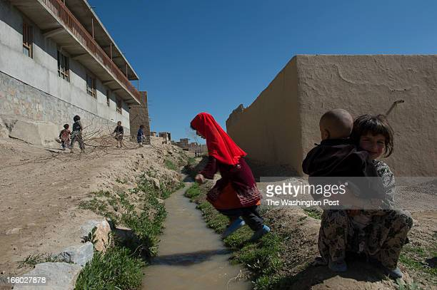 Children play while Afghan Army General Abdul Raziq surveys a village where recent kidnappings and Taliban activities have occurred in the Village of...