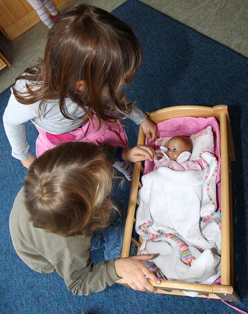 c746ac0d5baeb Children play with a baby doll at a day care center for children aged 12  months